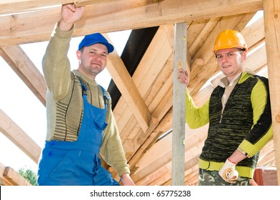 group of carpenters roofers workers in uniform at roofing works with level