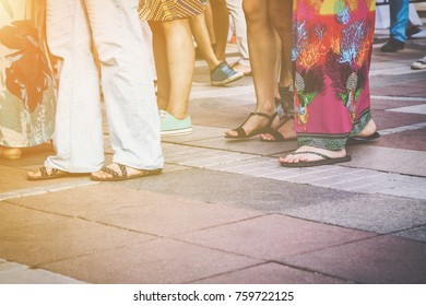 Group of casual men and women standing on paving in a low angle view of their feet in sandals, jeans, shorts and caftans or long summer skirts, with the sun glow in the left corner