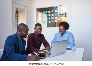 Group of casually dressed African colleagues talking together and using a laptop while sitting at a table in a modern office