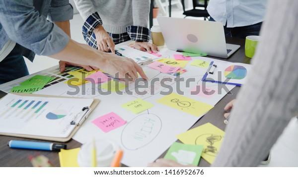 Grupo de empresarios con ropa informal discutiendo ideas en la oficina. Profesionales creativos reunidos en la mesa de reuniones para discutir los temas importantes del nuevo proyecto de inicio exitoso.