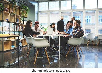 Group of casually dressed businesspeople discussing ideas in the office. Creative professionals gathered at the meeting table for discuss the important issues of the new successful startup project