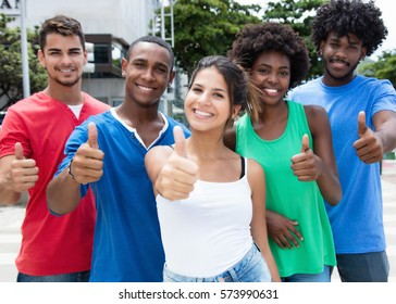 Group of caucasian and african american man and woman showing thumb up