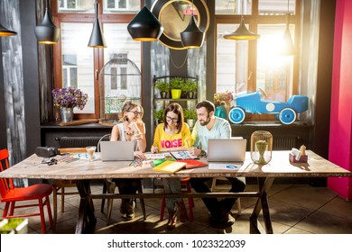 Group of caucasian coworkers dressed casually working together with documents and laptops at the big table in the beautiful cafe interior