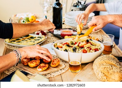 Group of caucasian friends enjoying together a happy lunch with italian meat lke pasta and pizza - beer and wine to have joy in friendship - wood table - home restaurant concept