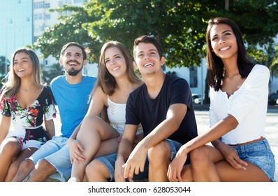 Group of caucasian and latin young adults looking around outdoor in the summer in the city