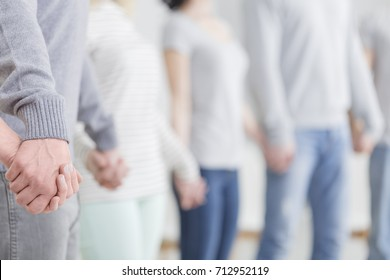 Group of caucasian people in bright clothes holding hands together