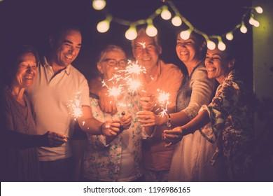 grupo de caucásicos amigos de diferentes edades celebran juntos un cumpleaños o una víspera de Año Nuevo por la noche en casa. luces y chispas con mujeres y hombres alegres divirtiéndose en la amistad