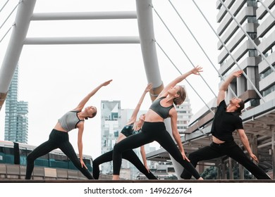 group of caucasian people having yoga workout outdoors in city