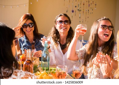 Group of caucasian people women friends celebrate together with table full of food and toasting with red wine - happiness and friendship for adult and young females at restaurant or home