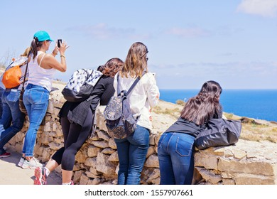 Group of caucasian students girls photograph enjoy by beautiful view Blue Grotto in Malta, rear view. Summer traveling concept: Zurrieq, Malta - May 1, 2019