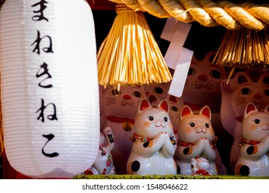 A group of ceramic Japanese lucky cats in the display cabinet (Japanese: Lucky Cat)
