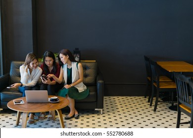 Group of charming  beautiful Asian women using smartphone and laptop, chatting on sofa at cafe, modern lifestyle with gadget technology or working woman on casual business concept