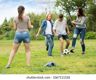 Group of cheerful active teenagers happily playing football together on green lawn in park
