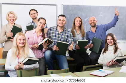 Group of cheerful adult students and coach posing at training session school. Selective focus