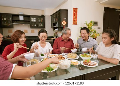 Group of cheerful Asian people enjoying good food at table served for Tet, couplets with best wishes for coming year in the background