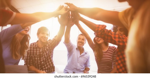 Group of cheerful business people giving high five while sitting creative office