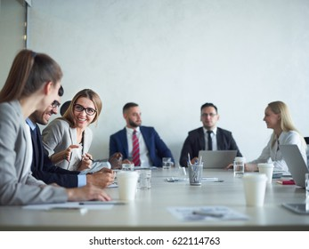 Group of cheerful business people smiling and chatting at meeting table in conference room