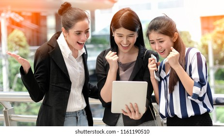 Group of cheerful businesswomen with tablet , startup project business meeting teamwork succesful concept. Attractive young women cheering with happiness on city background.