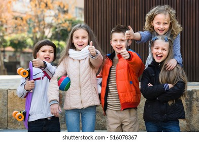 Group of cheerful children posing at urban street in sunny day