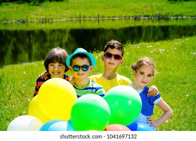 Group of cheerful children resting in the park. Outdoor activity. Summer holidays.