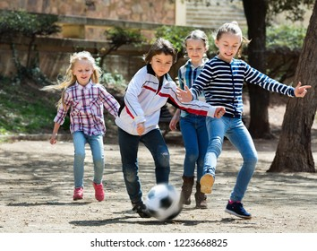 Group of cheerful children running after ball in urban location