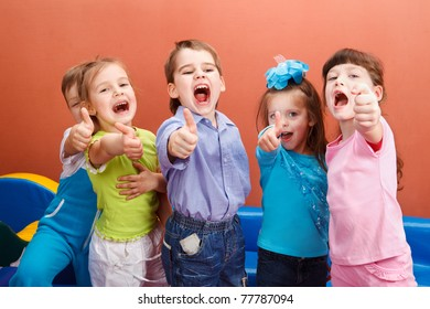 Group of cheerful children showing thumb up
