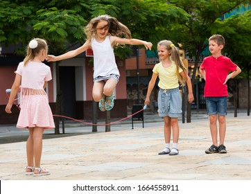 group of cheerful children skipping together with jumping rope on  urban playground