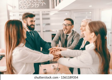 Group of cheerful corporate businesspeople in formal wear stacking hands at meeting in boardroom. Catch your people doing something right and let them know you appreciate it.