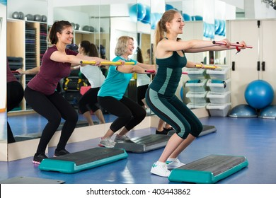 Group of cheerful different age women having aerobic train  in fitness club. Selective focus