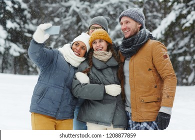 Group of cheerful excited young friends in puffy jackets laughing while taking selfie on smartphone in winter forest