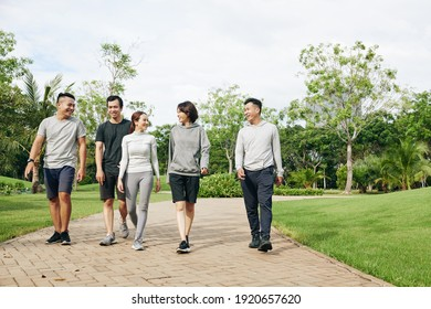 Group of cheerful fit Vietnamese men and women walking in park and discussing outdoor training they just had
