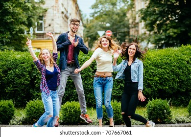 Group of cheerful four students jumping laughing and giving thumbs over green background - education, school, teamwork and people concept.