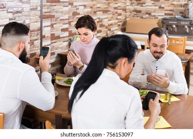 group of cheerful friends busy with phone ignoring dinner in restaurant