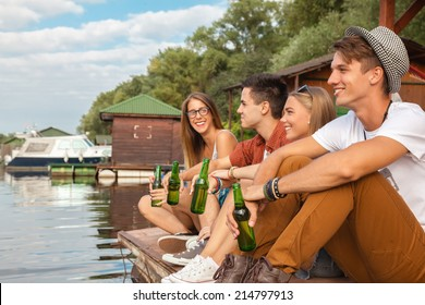 Group Of Cheerful Friends Chilling Near Lake
