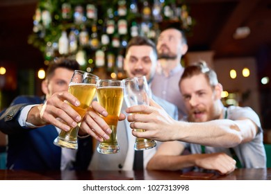Group of cheerful friends clinking beer glasses together while sitting at bar counter and  celebrating end of work week, focus on foreground