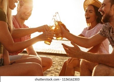 Group of cheerful friends dressed in summer clothing toasting with beer bottles at the beach