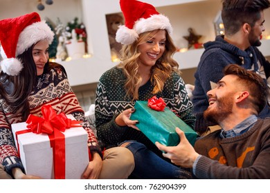 group of cheerful friends exchanging gift boxes at Christmas eve