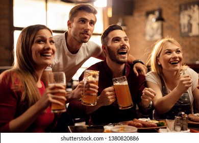 Group of cheerful friends having fun while watching sports game on TV and drinking beer in a bar.