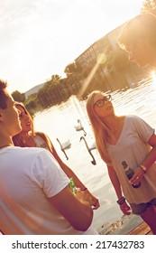 Group Of Cheerful Friends Having Fun Near Lake