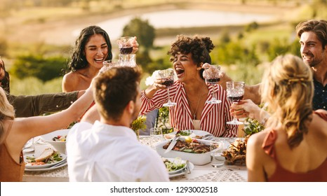 Group of cheerful friends having wine at dinner party. Multi-ethnic people having a get together outdoors.