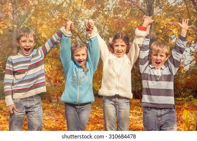 Group of cheerful friends holding hands in the autumnal park