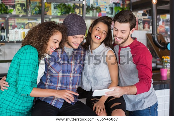 Group of cheerful friends laughing while watching mobile phone in restaurant