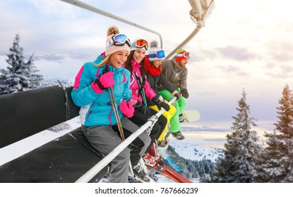 group of cheerful friends are lifting on ski-lift for skiing in the mountains