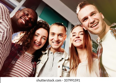 Group of cheerful friends looking at camera with toothy smiles