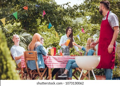 Group of cheerful friends partying and grilling together in the garden