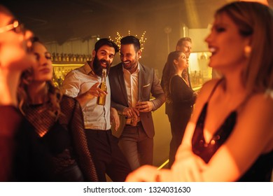 Group of cheerful friends partying at the nightclub