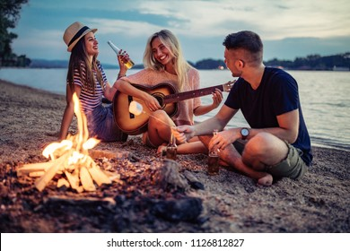 Group of cheerful friends playing the guitar and having fun on the beach by the bonfire. Warm tones.