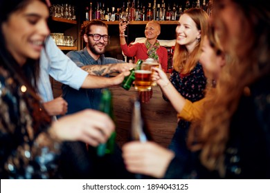 Group of cheerful friends standing near bar counter, drinking beer and chatting.