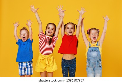 group of cheerful happy children on a colored yellow background