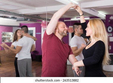 Group of cheerful happy young adults dancing salsa in club